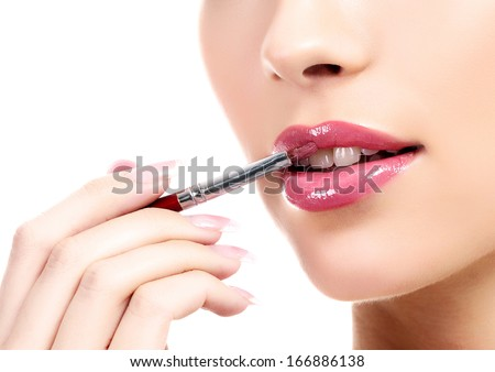 beautiful young woman applying lips makeup with cosmetic brush, white background, copyspace - stock photo
