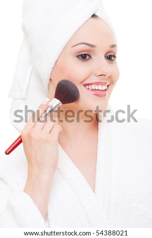 beautiful young woman applying make-up over white background - stock photo