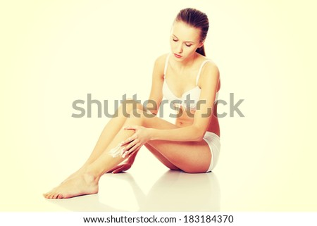 Beautiful young woman applying moisturizer cream on the legs  - stock photo