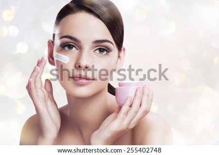 Beautiful young woman applying moisturizing creme, skin care concept / photoset of attractive brunette girl on blurred background with bokeh  - stock photo