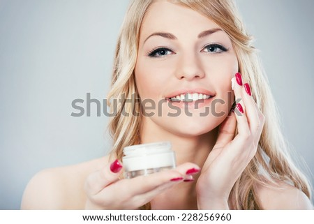 Beautiful young woman applying skin moisturizer on her face - stock photo