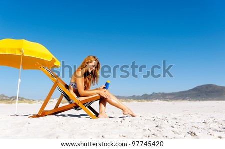 Beautiful young woman applying sunblock to her legs while sitting on a beach in summer. - stock photo