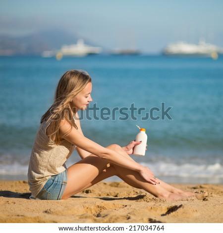 Beautiful young woman applying sunscreen on her legs - stock photo