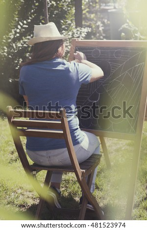 Beautiful young woman artist drawing sketch  on a blackboard with chalk in nature.