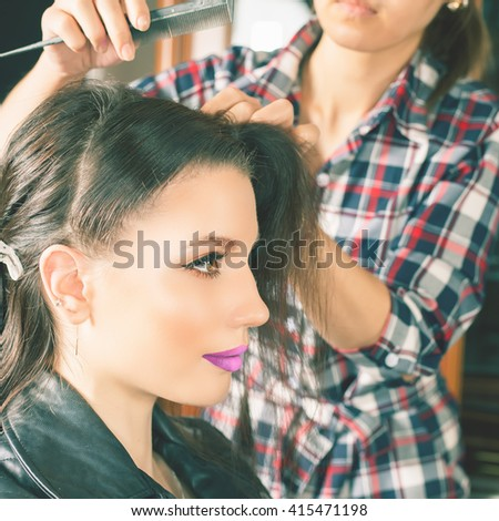 Beautiful young woman at beauty salon. Fashion hairstyle. Make up. Hair saloon. Hairdresser using hair spray - stock photo