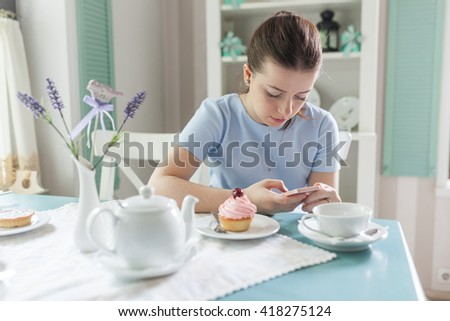 Beautiful young woman at french cafe drinking coffee and talking on the mobile phone. Flowers, window, cupcake, bag. Pretty girl leaning on the bar counter and text messaging with her mobile phone. - stock photo