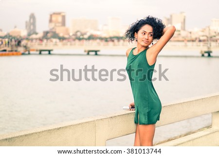 Beautiful young woman at pier standing in sensual posing - Slim body latina girl holding  mobile relaxing at city sea view - Asian fashion model wearing green short dress by the river - Beauty concept - stock photo