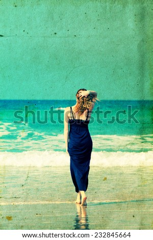 Beautiful young woman at the beach walking at the beach. Retro vintage instagram filter. - stock photo