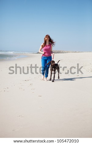 Beautiful young woman at the beach with a dog