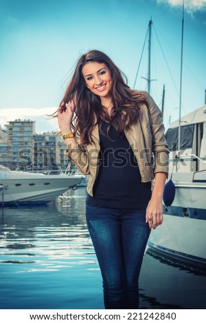Beautiful young woman at the harbor  - stock photo