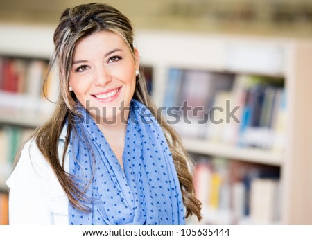 Beautiful young woman at the library smiling - stock photo