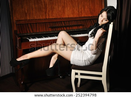 Beautiful young woman at the piano - stock photo