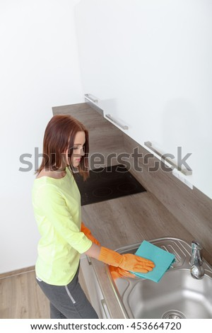 Beautiful young woman at work using rubber gloves. Cleans new kitchen. Woman with housework, cleaning the kitchen.