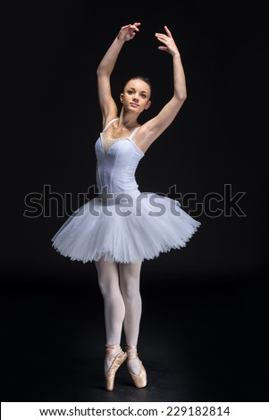 Beautiful young woman ballerina with tutu on the black background. - stock photo