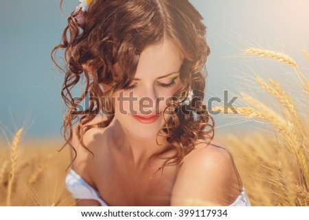 Beautiful young woman bask in the sunlight. She walks in a field of wheat. The girl admires nature and enjoys warm sunlight. She has a penetrating pensive gaze, beautiful eyes and curly hair.  - stock photo