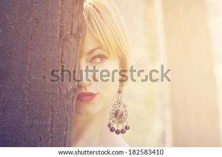 Beautiful young woman behind tree - stock photo