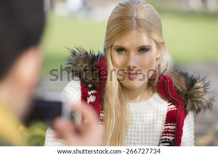 Beautiful young woman being photographed by man in park - stock photo