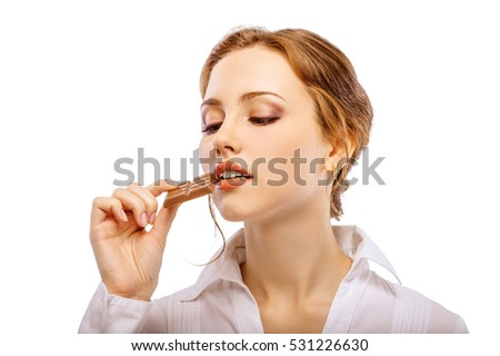 Beautiful young woman bites off chocolate, isolated on white background.