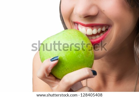 Beautiful young woman biting a green apple on a white background
