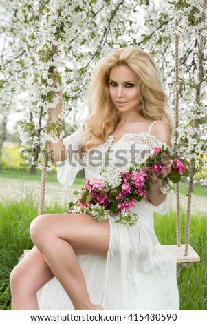 Beautiful Young Woman BLONDE MODEL SITS In gauzy dress on a swing suspended from the TREE blooming cherry among white flowers SPRING AND NATURE - stock photo