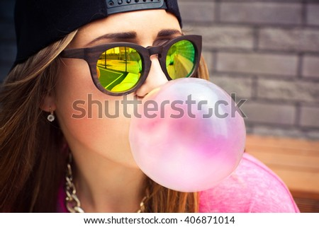 Beautiful young woman blowing a bubble gum balloon - stock photo