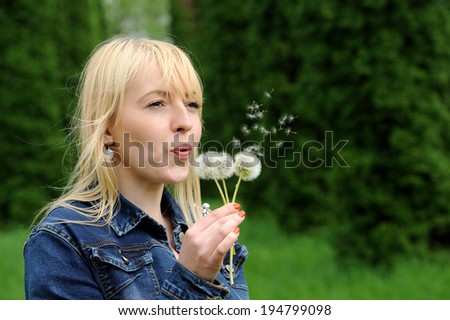 Beautiful young woman blowing a dandelion in park