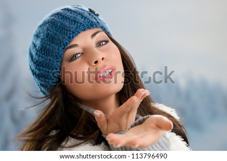 Beautiful young woman blowing a kiss in a winter day outdoor
