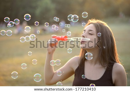 Beautiful Young Woman Blowing Bubbles Outside