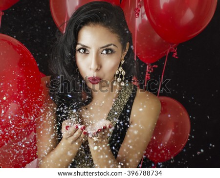 Beautiful young woman blowing confetti - red balloons background - stock photo