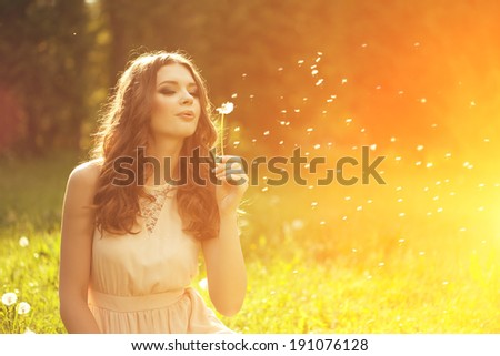 Beautiful young woman blowing  dandelion. Trendy young girl at sunset with flower  - stock photo