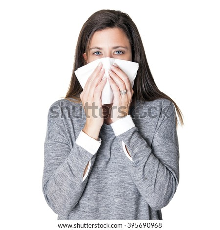 Beautiful young woman blowing her nose with a tissue - stock photo