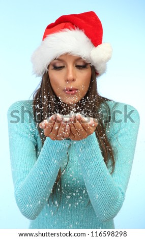 beautiful young woman blowing snow, on blue background