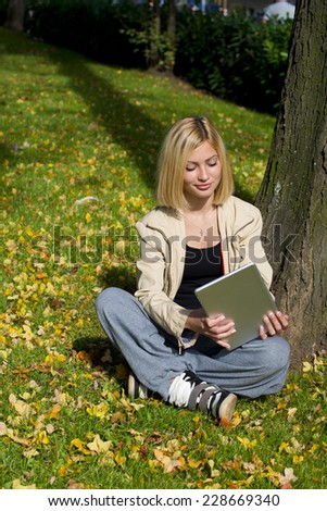 Beautiful young woman browsing tablet in the park while sitting on the grass.