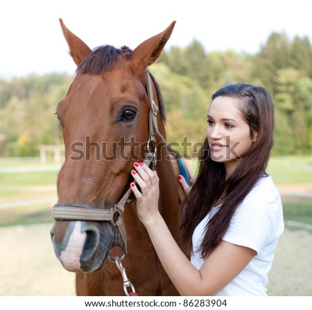 Beautiful young woman brushing a gorgeous horse