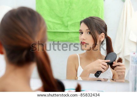 Beautiful young woman brushing her hair at bathroom