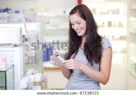Beautiful young woman buying perfume. Selective focus. - stock photo
