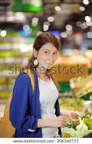 Beautiful young woman buying vegetables at supermarket