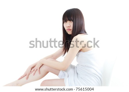 beautiful young woman caring for her legs, isolated on white background