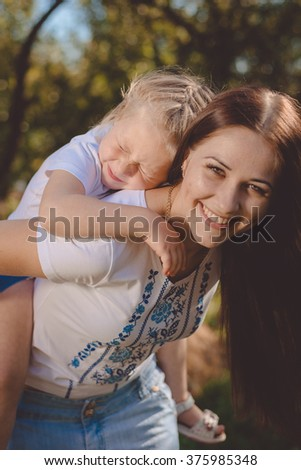 Beautiful young woman carries on her back little sister - stock photo