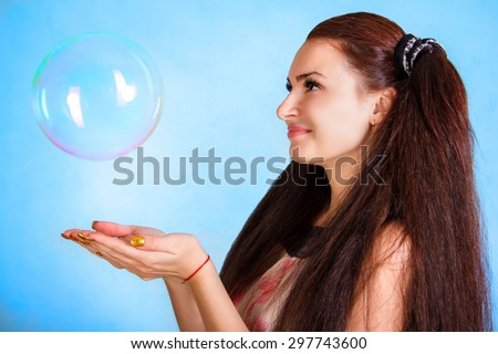 Beautiful young woman catching a huge soap bubble over cyan background - stock photo