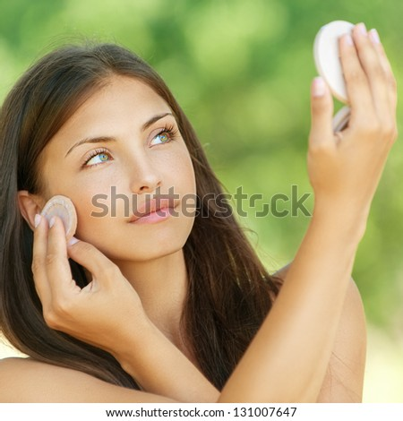 Beautiful young woman causes powder to skin, against summer green park.