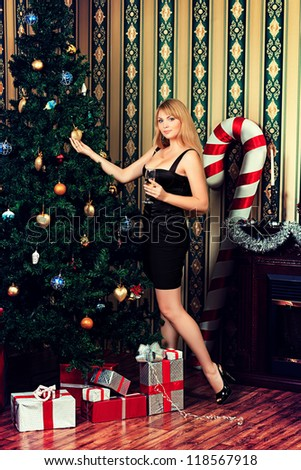 Beautiful young woman celebrating Christmas near the fireplace at home. - stock photo
