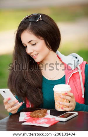 Beautiful young woman cell phone and coffee at outdoors, smiling girl with smartphone an tea at street cafe, happy female doing selfie and sms outdoor, soft light series - stock photo