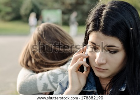 Beautiful young woman chatting on her mobile phone listening to the conversation with a concerned expression while her friend waits in the background - stock photo