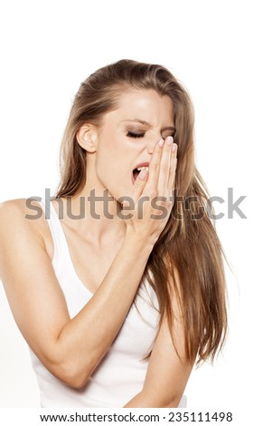 beautiful young woman checking her breath - stock photo