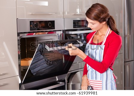 Beautiful young woman checking how her cake is doing in the oven - stock photo