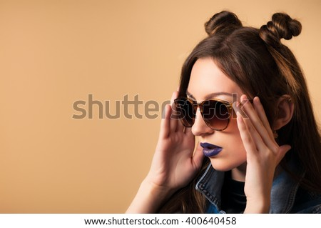 Beautiful young woman Chinoise in sunglasses. Spring-summer outfit. Hairstyle Coachella. Denim Jacket, dark lipstick. Cute Chinese, Asian-Caucasian woman, fashionable . Yellow background. Toned image.