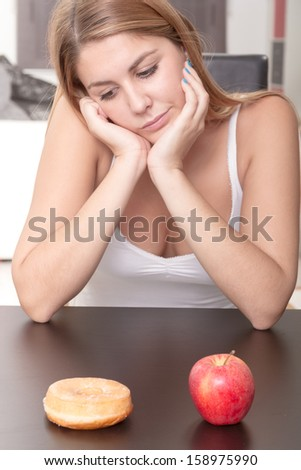 Beautiful Young Woman choosing between Fruits and Sweets in her house - stock photo