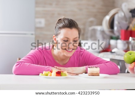Beautiful young woman choosing between fruits and sweets in her kitchen. - stock photo