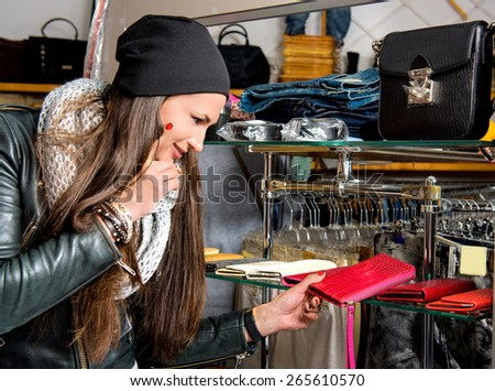 Beautiful young woman choosing leather purse in the shop - stock photo